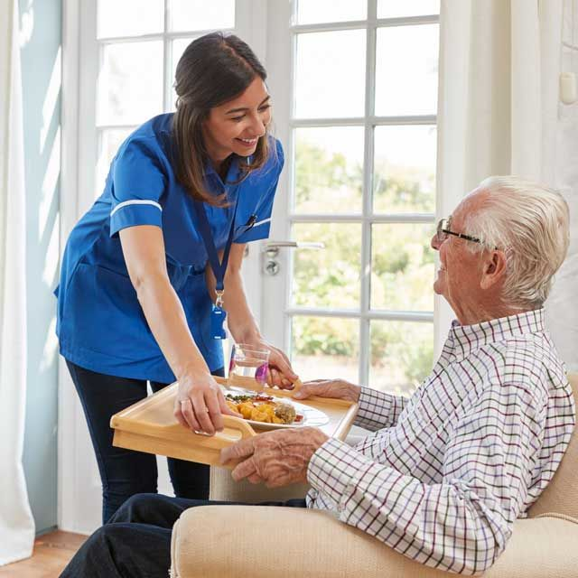 nurse serving dinner to senior man