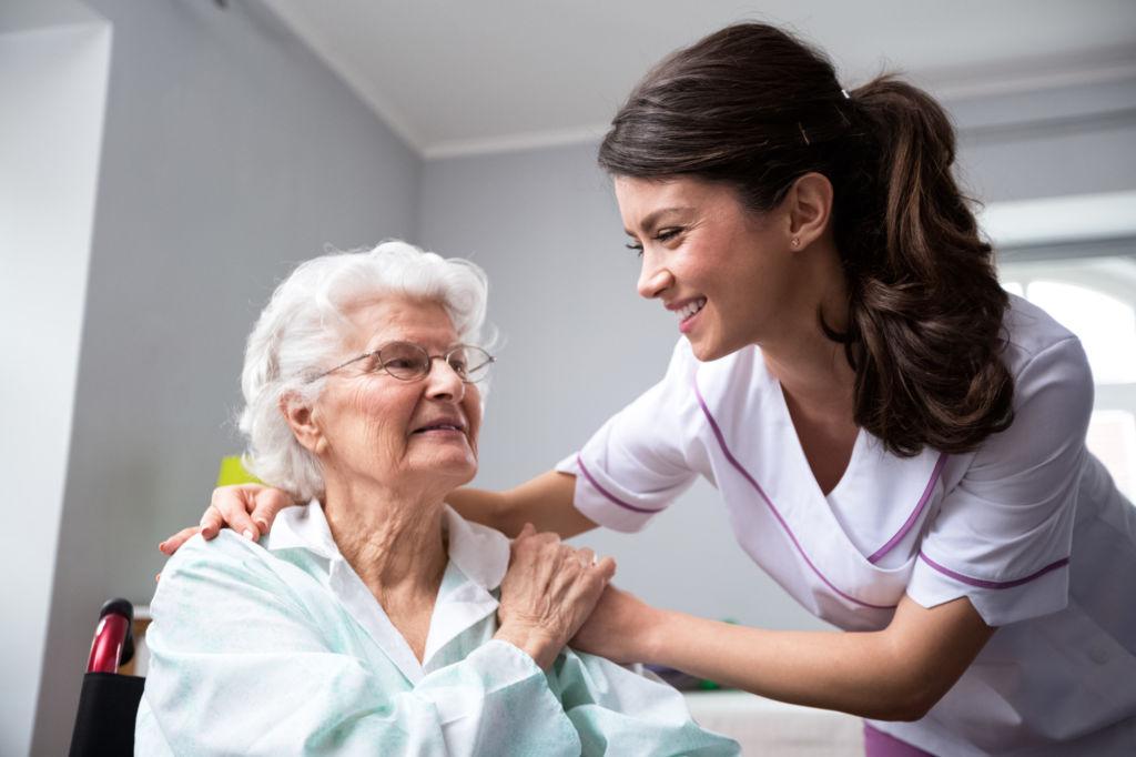 smiling nurse helping elderly patient