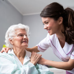 smiling nurse helping elderly patient