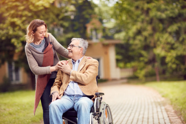 man on wheelchair being talked by daughter